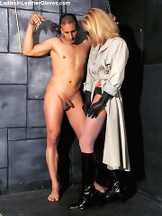 Sexy dominatrix in leather gloves ties up her submissive and plays with him