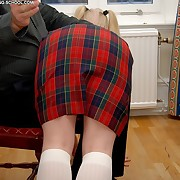 Stunning fair-haired schoolgirl receives a severe spanking on her bared buttocks
