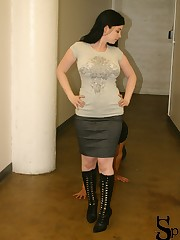 Sybil is in the hallway with her foot slave following her.