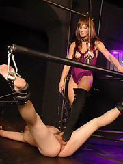 Mistress in purple fetish lingerie sitting on slave`s face and fucking him with a strapon