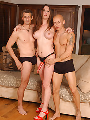 Strapon brunette poses with two sub guys