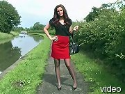 Sexy brunette posing outdoors with nylons and heels on