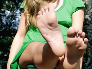 The pretty blonde teen showing her feet on seesaw
