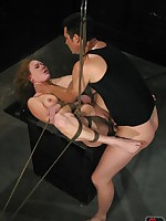 Bound submissive holds a lit candle in her mouth