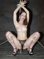 Pretty submissive girl bound in rope to pole by Domme