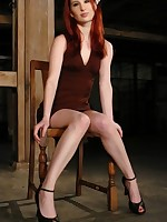 Lovely redhead strapped to the wall