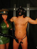 Male slave training by dominatrix in latex uniform