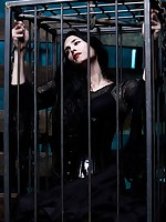 Goth girl in cage and stocks