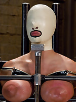 Hooded slave's breasts placed in a vise