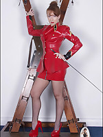 Domme in red latex poses on X cross