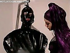 Domme in latex shaves male submissive's crotch.