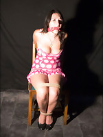 Girl is tied down to a chair with an abundance of rope