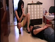 A nyloned domme standing on her sub