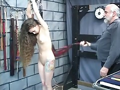 Master takes rope around slaves wrists to lash her ass with leather whip