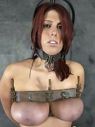 Slave is shackled and locked into the metal chastity belt, metal tit press