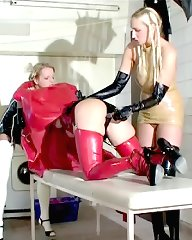 A tall blonde latex girl with huge tits joins our two latex princesses