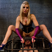 The latex mistress humiliates the caged boy