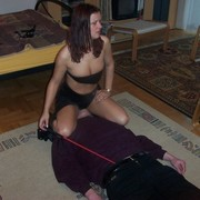 Misrtess in black skirt sat on slave