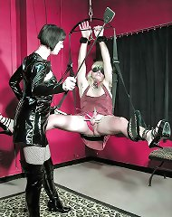 Latex domina trains her suspended mature sissy pinching his nuts and cock with pins