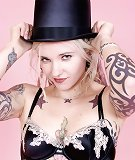 Dreadlocked tattooed goth blonde in top hat heels